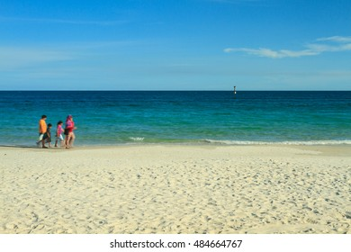White sand beach, clear blue sky, turquoise sea and tourists during a bright and sunny evening, Thailand. Copy space on the right.