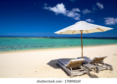 White sand beach with deckchairs and umbrella in tropical Island
