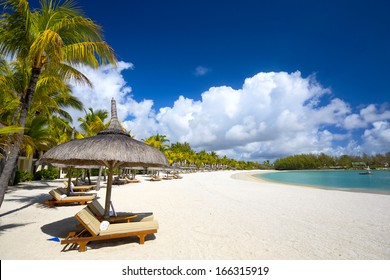 White sand beach with lounge chairs and umbrellas in Mauritius Island