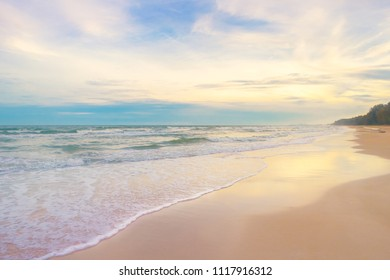 white sand beach meet tropical ocean with small waves and colorful sunset sky in Summer at Huai Yang, Thailand