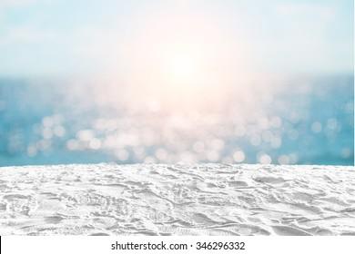 white sand beach on bokeh light sea background