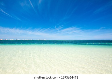 White sand beach with turquoise water and blue sky. Yachts and boats on the horizon. tropical beautiful background. Punta Cana, Bavaro