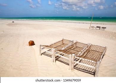 White  sand beach with wooden deck chairs in Zanzibar, Tanzania