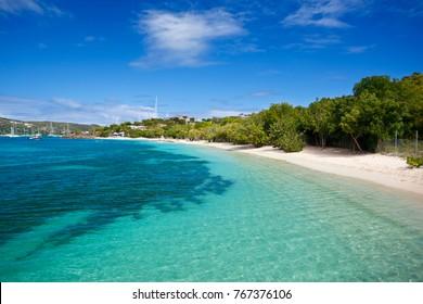 Weißer Sand und klares türkisfarbenes Wasser am Strand von Pigeon in Antigua.