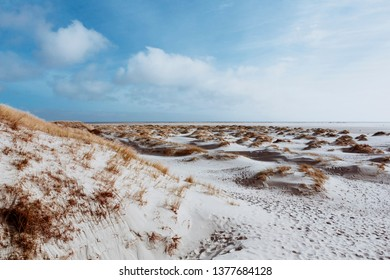 White sand dunes and dry grass on the shore with footprints on surface. Low angle landscape with bright cloudy sky at North Sea coast, Amrum, Germany, Schleswig-Holstein