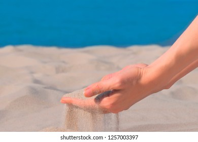 White Sand pours through fingers. Beautiful sandy beach background. Close up
