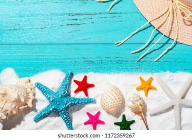 white sand and sea shells and starfishes and cap as summer holidays concepts
