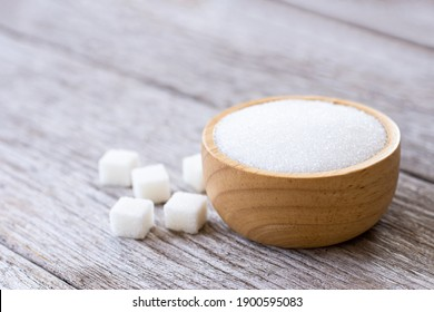 White sand sugar in wooden bowl  and cube sugar on wood table background.