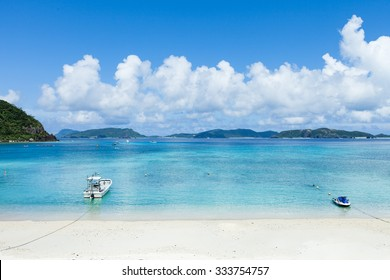 White sand tropical beach and clear blue water with boats, Kerama Islands National Park, Okinawa, Japan