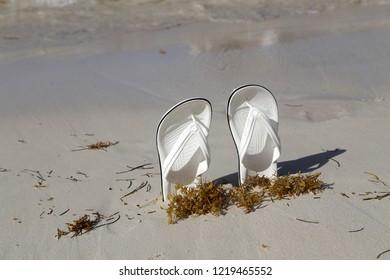 White sandals. White sandals on the beach.