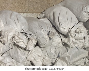 White sandbags stacked up tall, preparing for flooding and winter