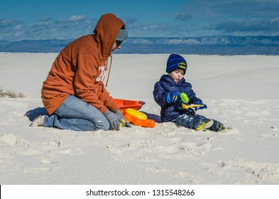 White Sands, NM / USA - 11-15-2014: Mother and young boy play with sand toys on a dune at White Sands National Monument in New Mexico.