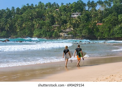 The white sandy beach and bay of Mirissa. Surfer with their boards on the way to the waves. The beach at the south coast is very popular among surfer. It is a top spot for aquatic sports