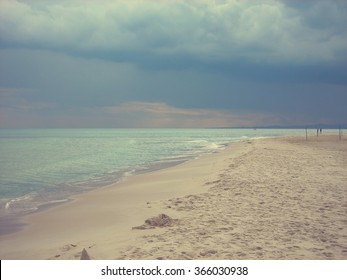 White sandy beach and blue sea in the Tunisian seaside resort Hammamet, on a cloudy day. Filtered image in faded, retro, Instagram style; nostalgic, vintage concept of holidays and travel.