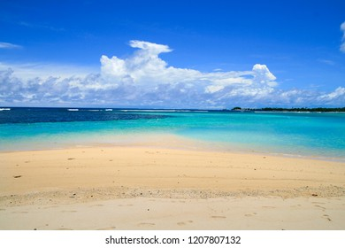 White sandy beach coast with turquoise coral sea water horizon and beautiful cloud sky, holiday destination concept background