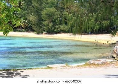 White sandy corner of Susupe Beach, Saipan A stretch of white sandy beach bordered by rocks at Susupe Beach in Saipan, Northern Mariana Islands
