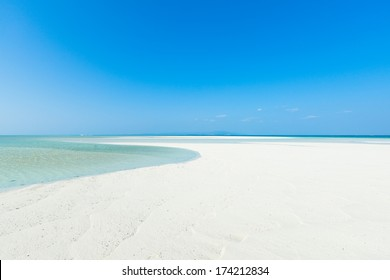White sandy tropical beach paradise with clear water and sunny blue sky, Taketomi Island of the Yaeyama Islands, Okinawa, Japan