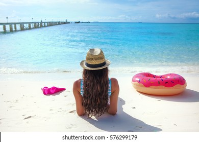 White sandy tropical beach, summer fun travel holiday water sports concept. Woman wearing hat lying down on the sand.