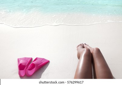 White sandy tropical beach, summer fun travel holiday water sports concept. Woman legs close up she is lying down on the sand.