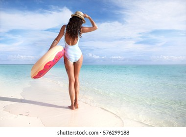 White sandy tropical beach and woman wearing hat and swimsuit. Summer fun travel holiday concept