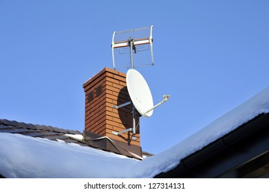 White satellite dish attached to the brown roof