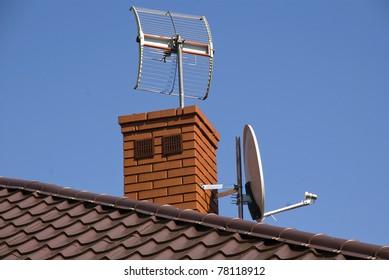 White satellite dish on brown roof