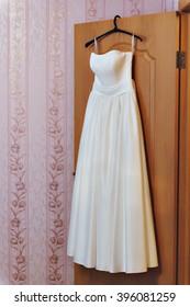 White satin wedding dress, hanging on a hanger on the door