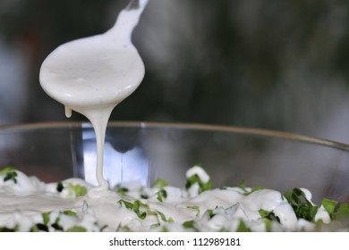 A white sauce  pour over green salad