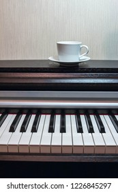 a white saucer and a cup of tea on the brown opened piano.