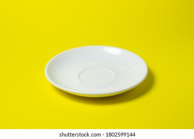 White saucer on a yellow background. An empty pink saucer lies on a yellow surface