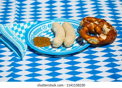 white sausage with sweet mustard and pretzel on blue white plate