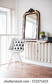 White scandinavian spring interior, hyacinths in a jar, minimalist room decor with chair and vintage mirror
