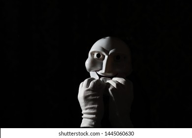 White scary mask on a black background with whites hands.