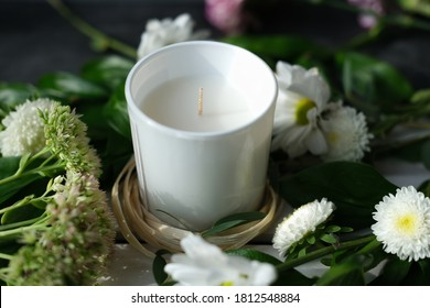 white scented candle and delicate flowers. home fragrances for relaxation and calm. flower fragrance for home. unbranded ceramic candle.