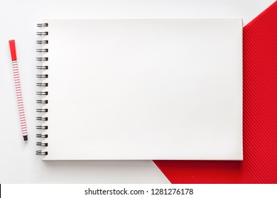 White school creative desk with red elements. Space for text. Mockup sketchbooks. Real photo, top view. School accessories. Minimal composition
