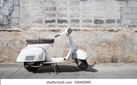 white  scooter stands parked near the concrete old wall,white scooter stands parked near the concrete old wall with blue sky background,white Classic Motorcycles
