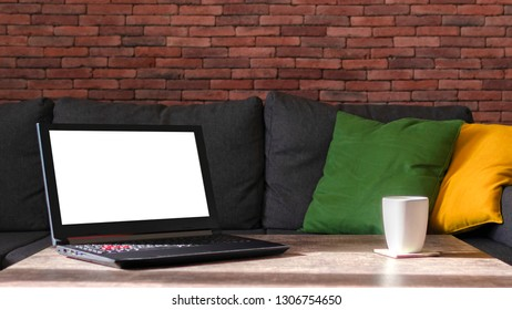 White screen gaming laptop and a white mug on a table, couch background