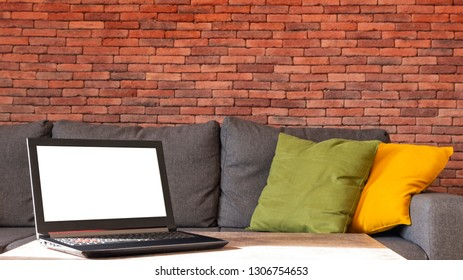 White screen gaming laptop on a table, couch background