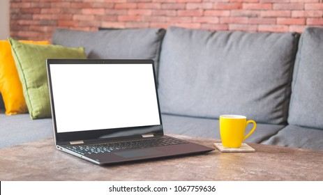 White screen laptop on a table by a couch mock up