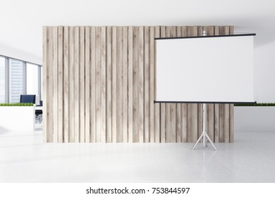 A white screen is standing next to a wooden wall in an open space office environment with large windows. 3d rendering mock up
