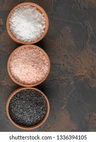 White (sea), pink (himalayan) and black salts in wooden bowls on dark background.