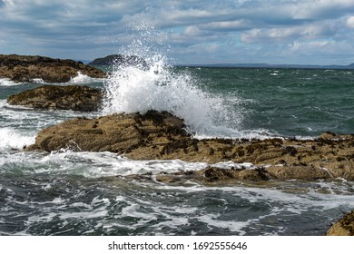 White sea spray crashing against the rocks on the coast of East Lothian near North Berwick on a windy stormy day