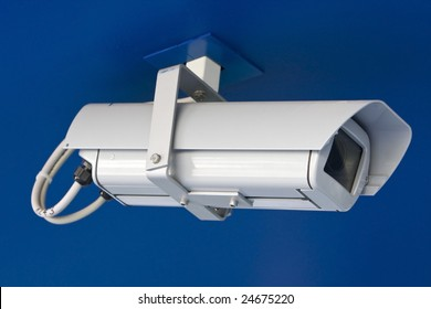 White security camera isolated on blue background.