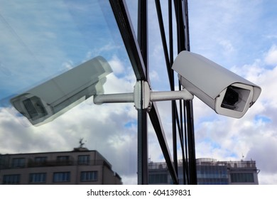 white security cctv camera on glass wall