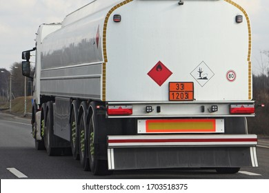 White semi truck fuel tanker with 33/1203 dangerous class sign and copy space place blank on barrel drive on asphalt highway on a spring day on blue sky background, side rear view ADR hazardous cargo - Shutterstock ID 1703518375