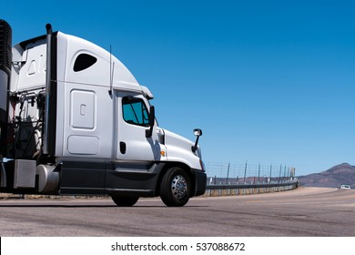 White semi truck going on the road with road fence, mountain and blue sky