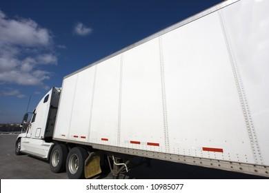 White Semi Truck parked under clouds.