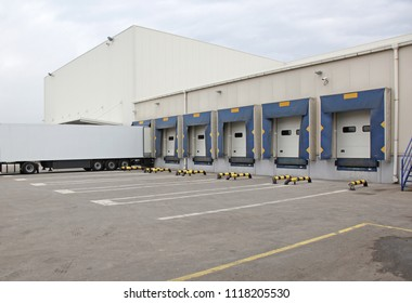 White Semi Truck Trailer at Warehouse Loading Ramp