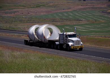 "White Semi-Truck pulling a loaded ""Oversize Load"" flatbed trailer down a rural Oregon Highway.  June 20th, 2017 Rural Oregon, USA"