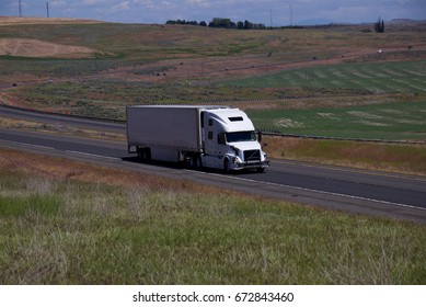 A White Semi-Truck pulling a white unmarked trailer along a rural Oregon highway.  June 20th, 2017 Rural Oregon, USA